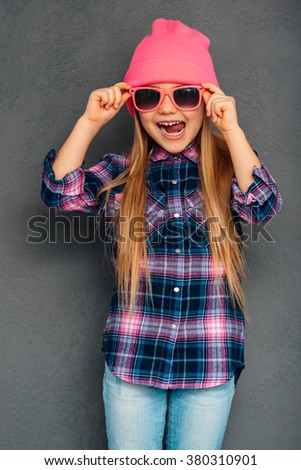 Little stylish beauty. Full length of cheerful little girl adjusting her sunglasses and grimacing while standing against grey background - stock photo