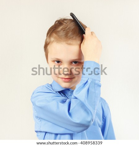 Little stylish boy in a bright shirt brushing her hair a hairbrush - stock photo
