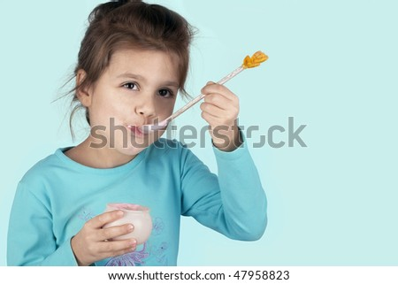 little successful laughing girl eating yogurt - stock photo