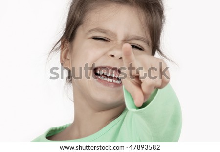 little successful laughing girl pointing. Isolated on white background - stock photo