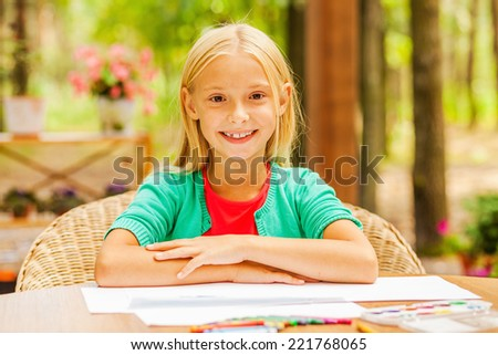 Little sunshine. Cute little girl looking at camera and smiling while sitting at the table with colorful pencils and paper laying on it - stock photo