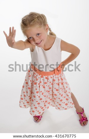 Little sunshine greets with everyone with spread cute smile, big blue eyes. Young girl put her hand on the waist. Isolated. - stock photo