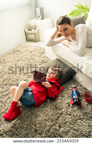 Little superhero boy playing videogames and mother lying down on sofa in the living room. - stock photo