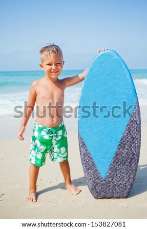 Little surfer. Boy with surfboard standing near ocean. - stock photo