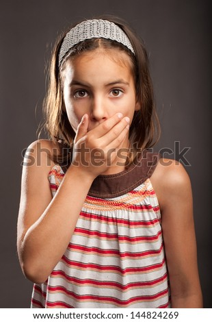 little surprised girl covering mouth with her hand - stock photo