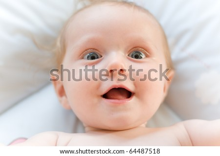 little sweet baby laughing with big eyes and open mouth - stock photo