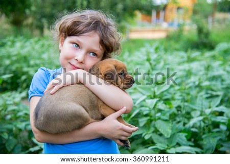 Little sweet curly girl with a red puppy on hands