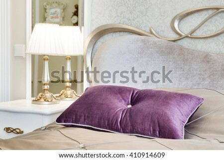 little table with a lamp and a bed with pillows in a modern bedroom - stock photo