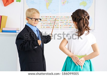 Little teacher showing flags of different countries to a girl - stock photo