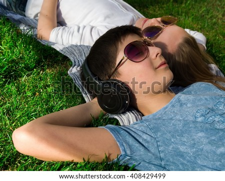 Little teenage boy and girl are lying on grass and boy wears earphones chill-out top view - stock photo