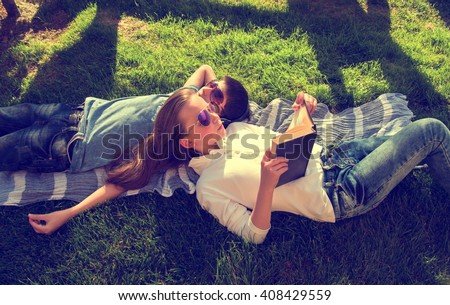 Little teenage boy and girl are lying on grass, girl reads book and boy wears earphones chill-out - stock photo