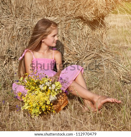 Little teenager child girl  in dress with flowers in summer day near haystack - stock photo