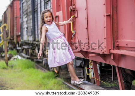 little thai girl hanging on the side of a freight train like a blind passenger