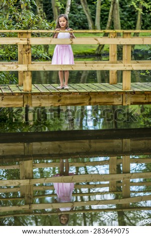 little thai girl on a bridge with reflection below - stock photo