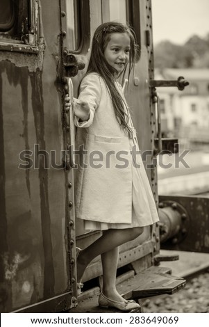 little thai girl on an old train, sepia - stock photo