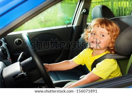 Little thee years old boy playing to be a driver in parents car  steering the wheel - stock photo