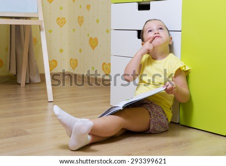 Little thinking girl with book at home - stock photo