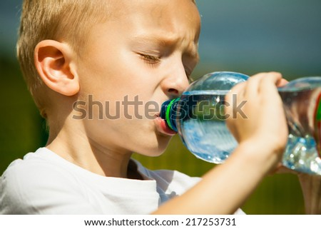Little thirsty boy child drink water from plastic bottle, outdoor