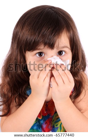Little three year old girl having the sniffles and wiping her nose with tissue from being sick or allergies - stock photo