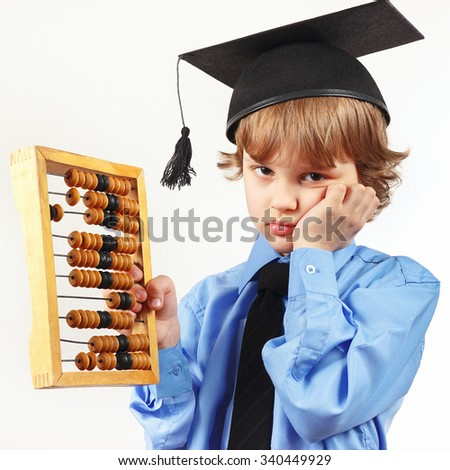 Little tired boy in academic hat with old abacus on a white background - stock photo