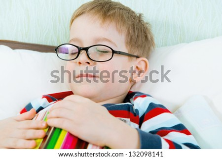 Little tired boy in glasses sleeping with book in bed - stock photo