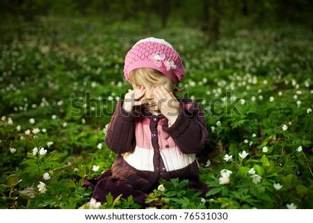 little tired girl sitting in flowers field - stock photo