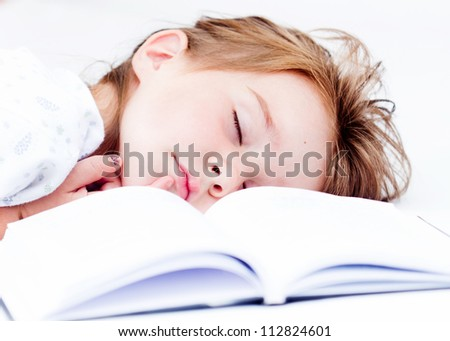 Little tired girl sleeping after reading - stock photo