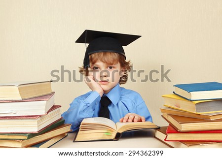 Little tired professor in academic hat studies an old books - stock photo