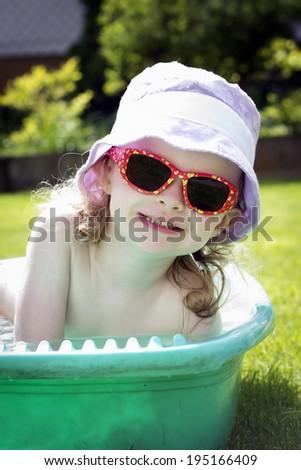 Little toddler bathing in the garden - stock photo