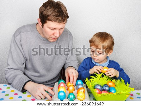 Little toddler boy and his dad having fun with preparing eggs for Easter egg hunt, traditional action in Germany for Eastern holiday, indoors. Family celebrating Easter holiday. - stock photo