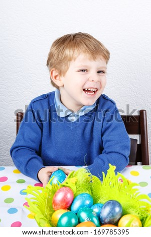Little toddler boy being happy about Easter egg hunt, traditional action in Germany for Eastern holiday