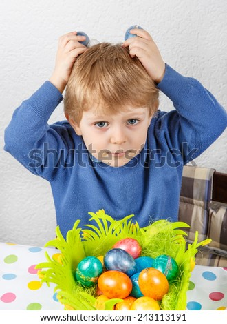 Little toddler boy being happy about Easter egg hunt, traditional action in Germany for Eastern holiday - stock photo