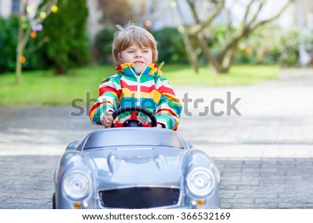 Little toddler boy driving big toy old vintage car and having fun, outdoors. Active leisure with kids outdoors  on warm spring or autumn day. - stock photo