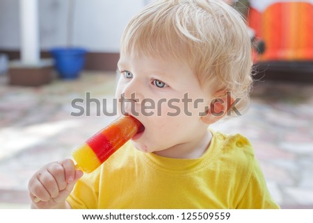 Little toddler boy eating colorful ice cream in summer - stock photo