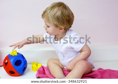 Little toddler boy of one year  playing with educating puzzle toys indoor. Kid on check-up of skills at doctor. - stock photo