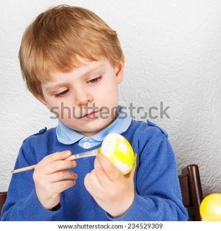 Little toddler boy painting colorful eggs for Easter hunt, traditional action in Germany for Eastern holiday, indoors. Square format. - stock photo