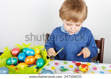 Little toddler boy painting colorful eggs for Easter hunt, traditional action in Germany for Eastern holiday, indoors - stock photo
