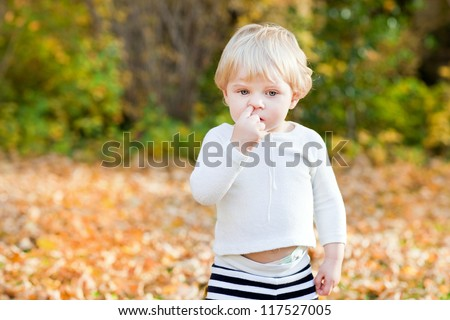 Little toddler boy picking his nose in autumn park