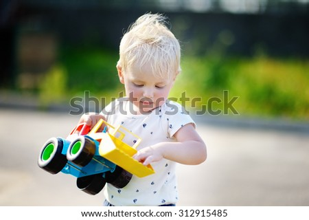 Little toddler boy playing with bright car toy - stock photo