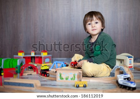 Little toddler boy playing with wooden railway, indoors.  - stock photo