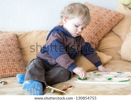 Little toddler boy playing with wooden toys indoor - stock photo