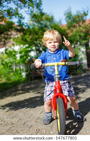 Little toddler boy riding on his bicycle  in summer garden