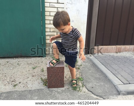 Little toddler boy stepping on granite block