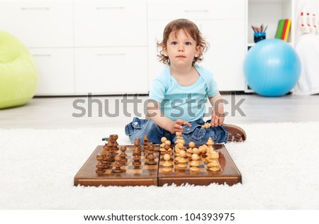 Little toddler boy with chess board sitting on the floor
