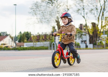 Little toddler child having fun and riding his bike  in the city - stock photo