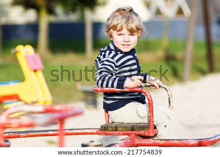Little toddler child having fun on old carousel on outdoor playground. - stock photo