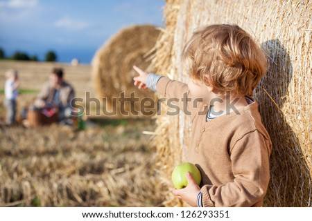 Little toddler eating apple with a big hay bale on field in summer, Germany. Family making picnic on background