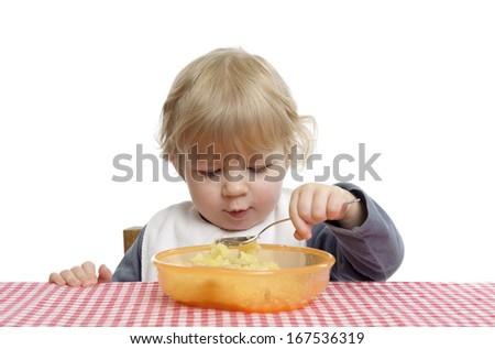 Little toddler eating by herself