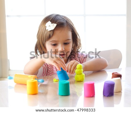 Little toddler girl creating toys from playdough - stock photo
