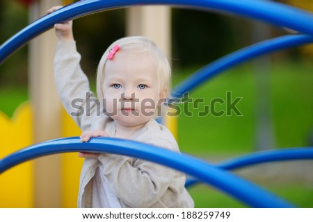Little toddler girl having fun at a playground - stock photo